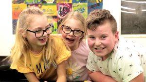 Three children smile at the camera