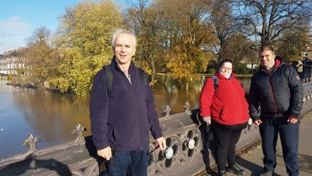 Three people stand by the river in York