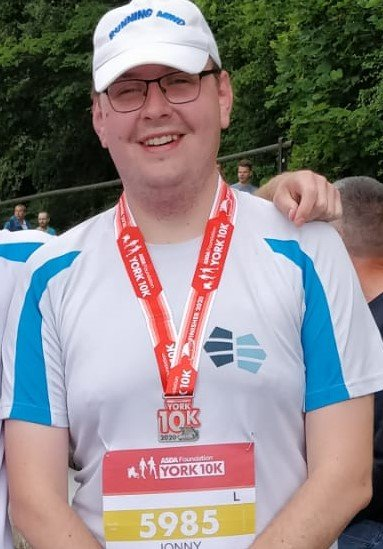 Jonny smiles at the camera with his York 10K medal round his neck